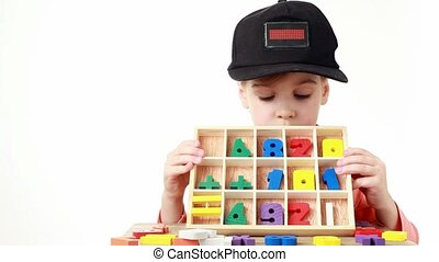 girl in cap with LED display box with cells containing wooden figures