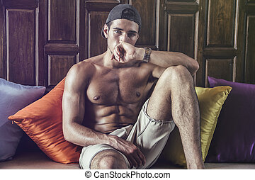 Shirtless muscular young man on sofa - Shirtless athlete...