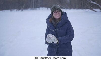 Girl smiling throwing snow - Girl throwing snow smiling...
