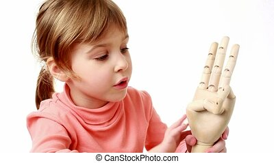 girl flexes fingers of wooden model of human hand and brings it closer to screen
