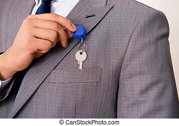 Businessman in real estate concept with home key