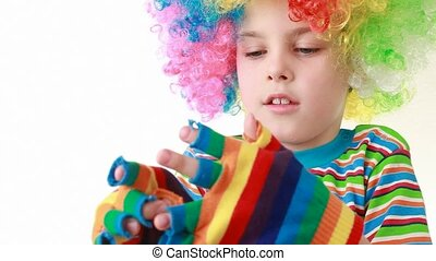 Boy in ridiculous wig wears gaudy striped gloves