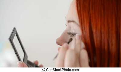 Beauty woman applying makeup - Beauty red woman applying...
