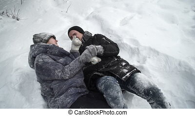 Girl and boy fooling around and lie in the snow city park....