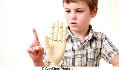 boy flexes fingers of wooden model of human hand