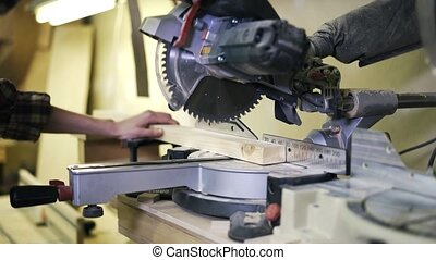 A woman is working with wood using a special machine. Real...