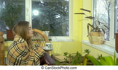 cheerful young girl sits in a wicker chair looking out the windows with snowfall behind it and drinks hot tea
