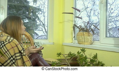young charming woman sits in the wicker chair looking out...
