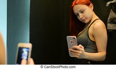Young woman taking selfie in fitting room - Young slim red...