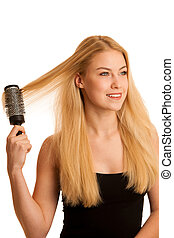 Beautiful blonde woman brushing her hair as a sign og hair...
