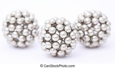 figures consisting of metallic balls are shooted with...