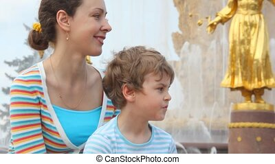 Mother and son sit near Fountain Friendship of Peoples