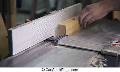 A craftsman is working with wood using a special industrial...