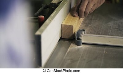 A craftsman is working with wood using a special power tool....