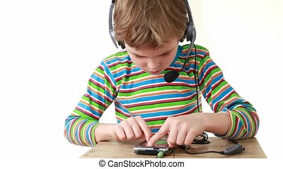 Boy in headset, sitting, listens music on PDA