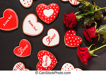 Beautiful gingerbread heart and red roses on a black...