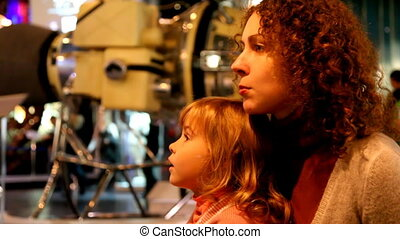 mother talking with her daughter in the space museum with a...