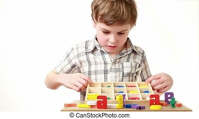 boy raises box with cells containing figures and shows...