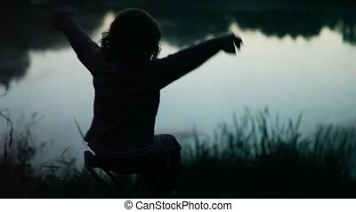 girl sits on chair at pond in wood