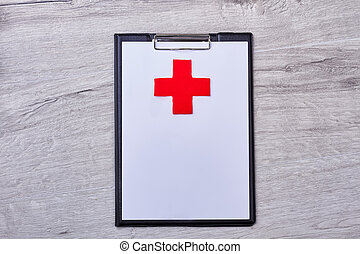 Clipboard with a red cross.