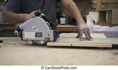 A craftsman is working with wood using a power Circular Saw....
