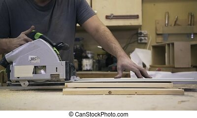 A craftsman is sawing a wooden bar using an Circular Saw - A...
