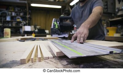 A craftsman is sawing a wooden bar. A concept of master...