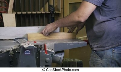A craftsman is working with wood using a special machine....