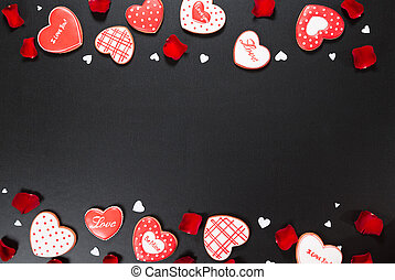 Beautiful gingerbread heart and red petals roses on a black...