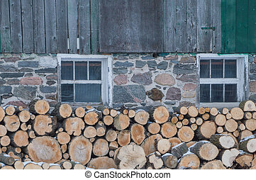 Neatly stacked firewood by an old Ontario Barn in winter -...