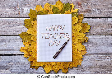 Dry leaves, pen and notebook. Teacher's Day celebration.