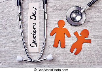 Stethoscope, stickmen on wooden background.