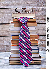 Glasses and tie. Books on wooden shelf. Men's business...