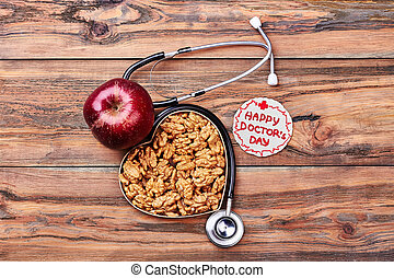 Apple, greeting card and stethoscope. Walnuts in a box....