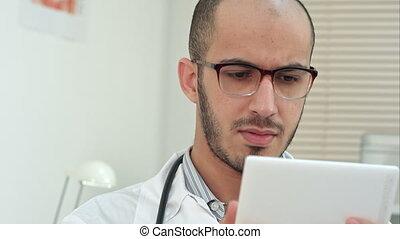 Male medical worker using digital tablet. Close up shot....
