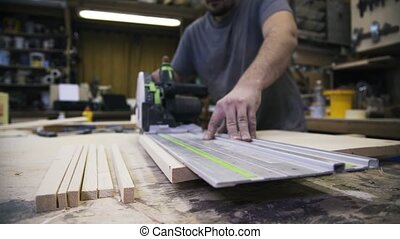 A craftsman is sawing a wooden bar using a power saw. Real...