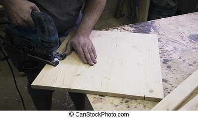 A craftsman is sawing a wooden bar using a fretsaw. Real...
