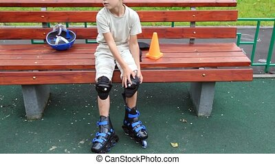 boy sits on bench in rollers standing and dresses protection...