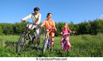 family with daughter sits on bicycles in field - happy...