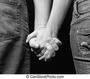 engaged couple holding on hands - view from backside
