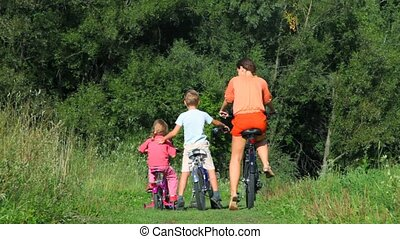 mother with son and daughter sits on bicycles backs to...