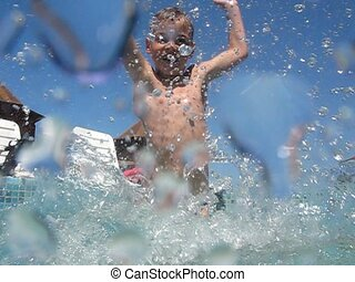 boy in outdoor swimming pool splashes water