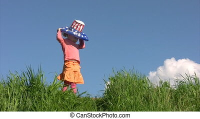 girl in american flag hat stands on meadow against sky