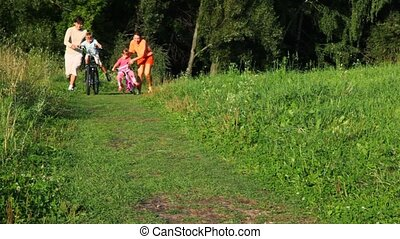 parents helps a kids riding bicycles in park - family of...