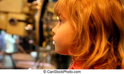 little girl in the space museum, listening and watching the...