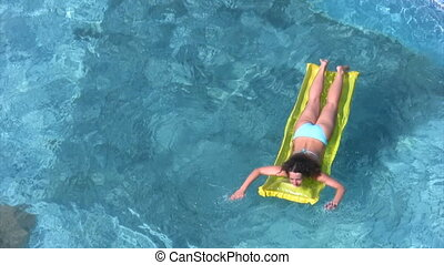 woman lying on inflatable mattress and oaring in swimming...
