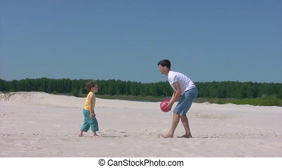 man and boy plays with ball on beach - young man and little...