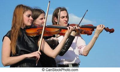 three musicians plays violin outdoors, sky with birds in...