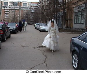 bride in white dress comes on street of city - happy bride...