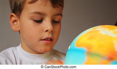 boy looks at shone globe and rotates it indoors close up